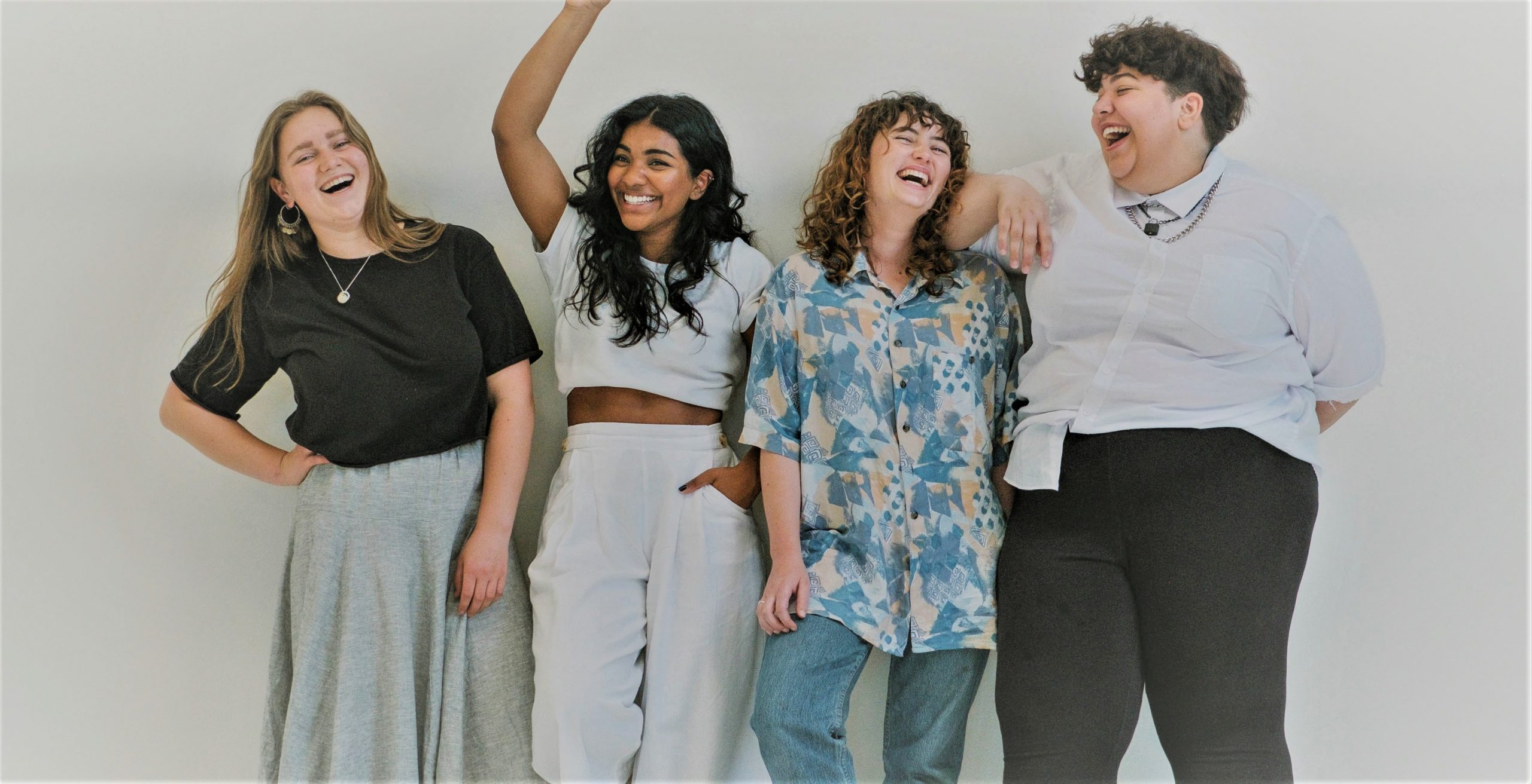 Four women laughing together.